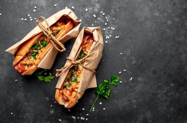 Hot dog francesi dal negozio confezionato in carta, cotto con formaggio e senape su uno sfondo di pietra con copia spazio per il testo