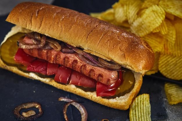 Hot dog - salsiccia calda nidificata in un panino con cetrioli, peperoncino e cipolle
