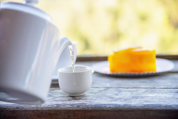 Hot mangiare tazza e torta arancia con sfondo verde natura