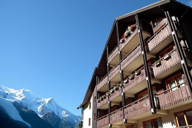 Hotel chalet alpino europeo tradizionale, vista sulle alpi in lontananza. copia spazio nel cielo blu.