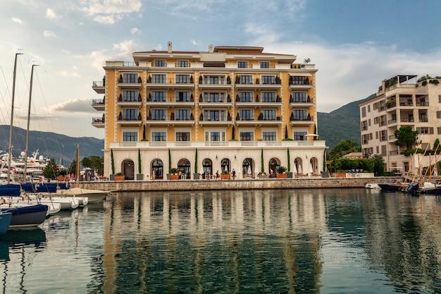 Hotel luxuri in un porto turistico con yacht bianchi come la neve. vista frontale.
