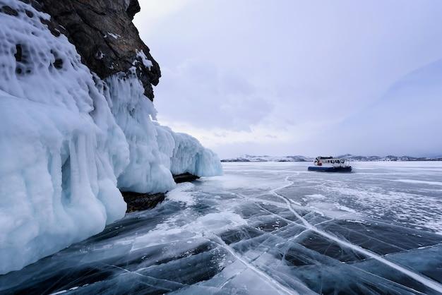 Hovercraft sul ghiaccio del lago baikal ghiacciato vicino a una roccia coperta di ghiaccio