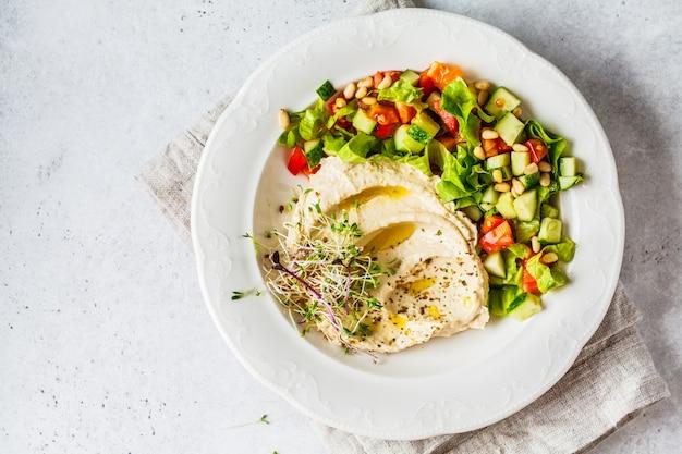 Hummus con insalata di verdure e germogli in zolla bianca,