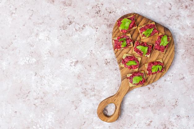 Hummus di barbabietola canapes withgreen pepe fette e prezzemolo sul tagliere sulla superficie della luce
