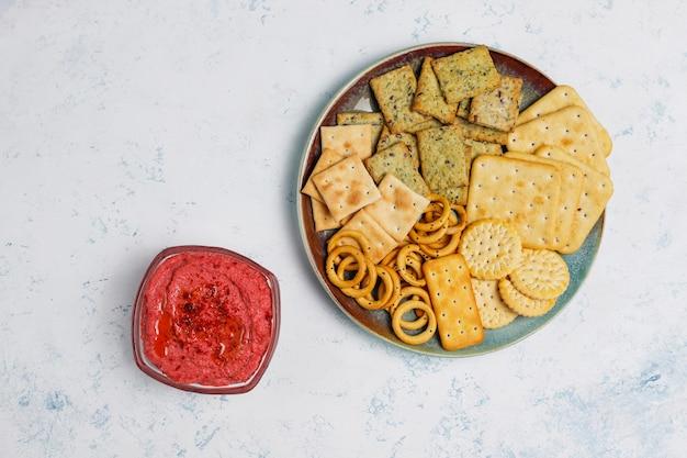 Hummus di barbabietola sul tagliere con i biscotti salati sulla superficie della luce