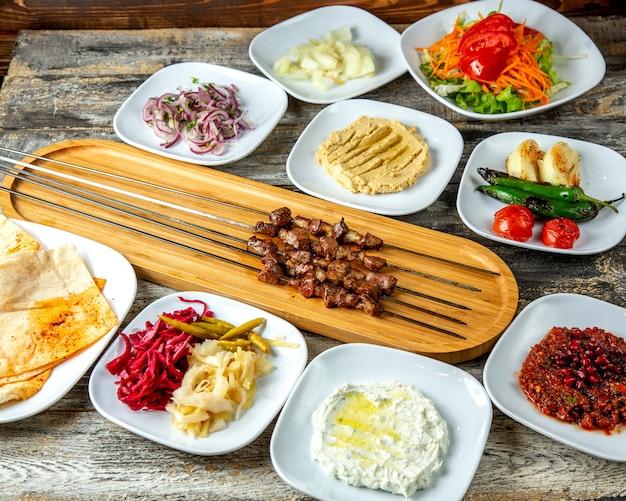 Hummus di kebab del fegato sottaceti la vista laterale del lavash della cipolla del pomodoro del pepe dell'insalata verde