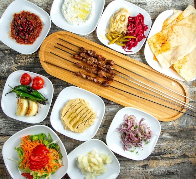 Hummus di kebab del fegato sottaceti la vista superiore del lavash della cipolla del pomodoro del pepe dell'insalata verde