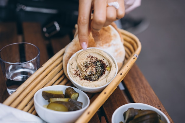 Hummus fresco delizioso, pane pita e cetrioli sottaceti