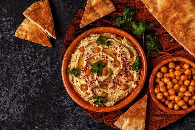 Hummus guarnito con prezzemolo e servito con pane pita
