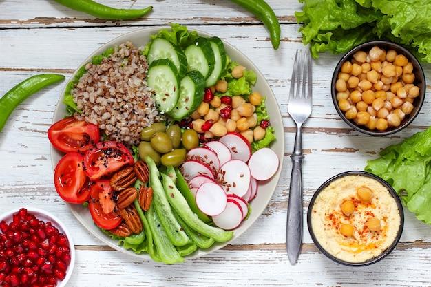 Hummus in ciotola, bastoncini di verdure, ceci, olive.