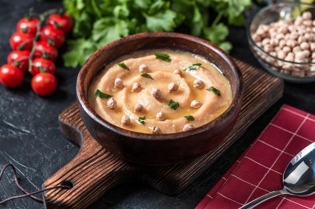 Hummus in un piatto di legno marrone.