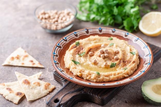 Hummus nel piatto di argilla marrone