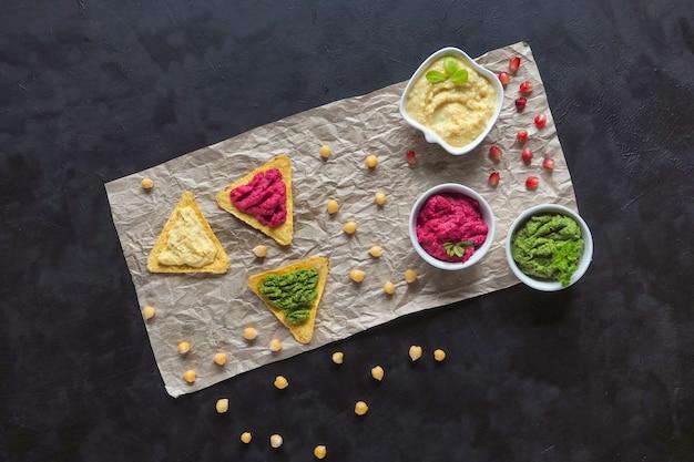 Hummus tradizionale spalmato su patatine di mais su un tavolo nero. antipasto di hummus.