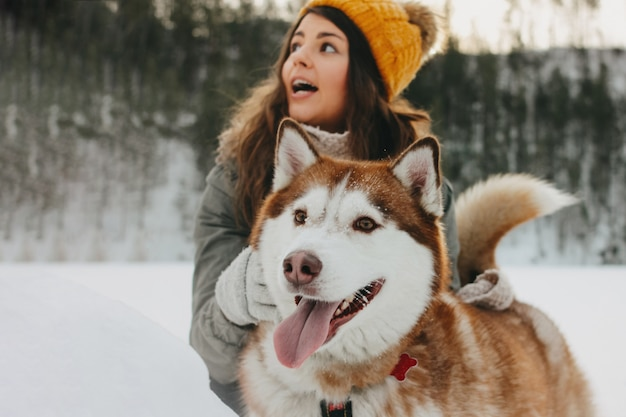 Husky rosso del cane con la sua ragazza castana della padrona in foresta all'aperto nella stagione fredda