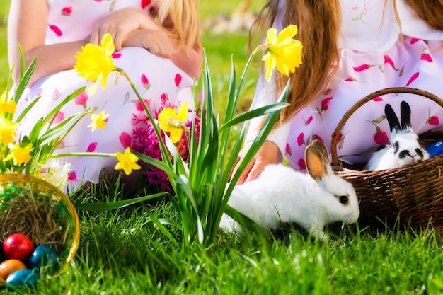 I bambini a caccia di uova di pasqua con coniglietto