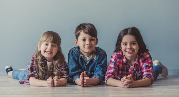 I bambini allegri in abbigliamento casual stanno esaminando la macchina fotografica.