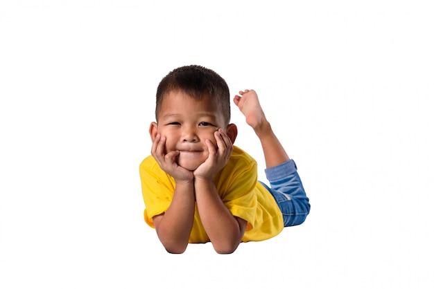 I bambini asiatici felici che si trovano sul pavimento hanno isolato la priorità bassa bianca