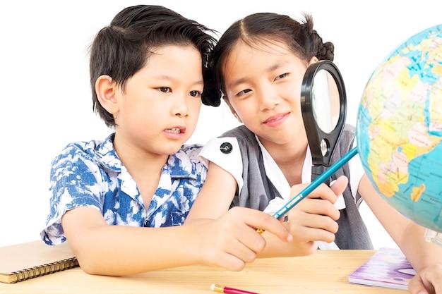 I bambini asiatici stanno studiando il globo usando la lente di ingrandimento su sfondo bianco
