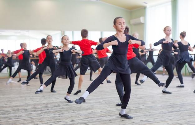 I bambini ballano con un istruttore in una grande sala di allenamento.