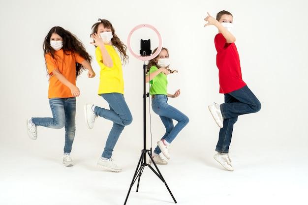 I bambini ballano positivamente con maschere mediche. giornata mondiale dei bambini