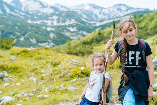 I bambini che fanno un'escursione in una bella giornata estiva nelle montagne delle alpi in austria, riposano su una roccia e ammirano una vista meravigliosa sulle cime delle montagne. vacanza attiva in famiglia con i bambini. divertimento all'aria aperta e attività salutare