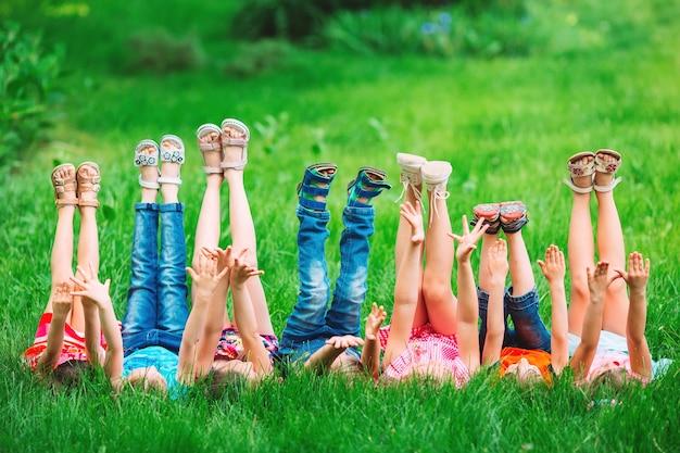 I bambini che si trovano sull'erba verde nel parco in una giornata estiva con le loro gambe sollevate verso il cielo.