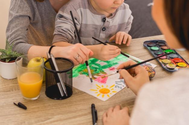I bambini con la mamma dipingono le immagini con colori ad acqua e pennello