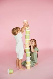 I bambini costruiscono una torre di scatole di carta colorate su uno sfondo rosa.