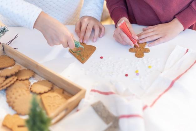 I bambini decorano i biscotti di natale allo zenzero con le matite di zucchero