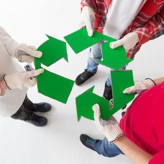I bambini del primo piano che tengono riciclano il segno
