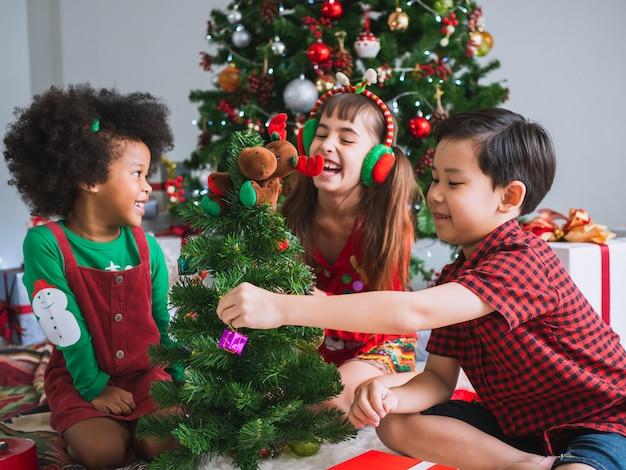 I bambini di molte nazionalità stanno celebrando il giorno di natale, i bambini sotto l'albero di natale con divertimento e felicità
