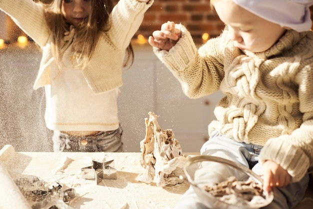 I bambini divertenti della famiglia felice stanno preparando la pasta, giocando con la farina nella cucina