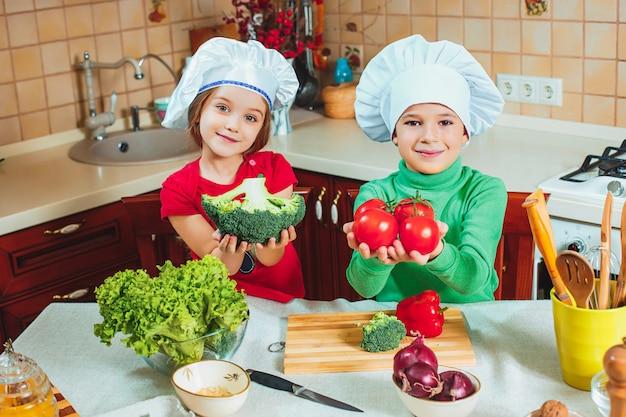 I bambini divertenti della famiglia felice stanno preparando un'insalata di verdure fresca nella cucina