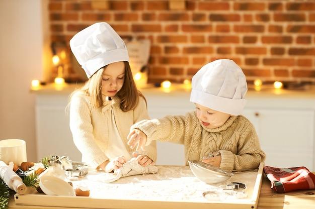 I bambini divertenti felici della famiglia stanno preparando la pasta