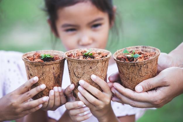I bambini e le mani dei genitori che tengono le giovani piantine dentro riciclano insieme i vasi di fibra