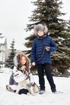 I bambini escono e giocano con il cane husky in inverno. i bambini si siedono sulla neve e accarezzarono il cane husky. camminare