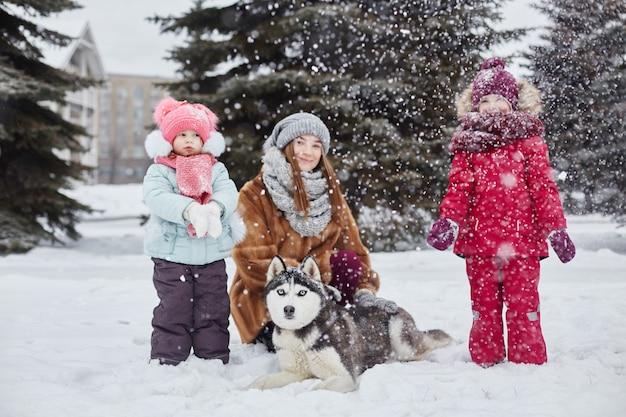 I bambini escono e giocano con il cane husky in inverno. i bambini si siedono sulla neve e accarezzarono il cane husky. passeggiata nel parco in inverno, gioia e divertimento, cane husky con gli occhi blu. russia, sverdlovsk,
