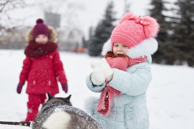 I bambini escono e giocano con il cane husky in inverno