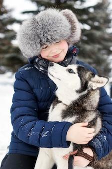 I bambini escono e giocano con il cane husky in inverno.