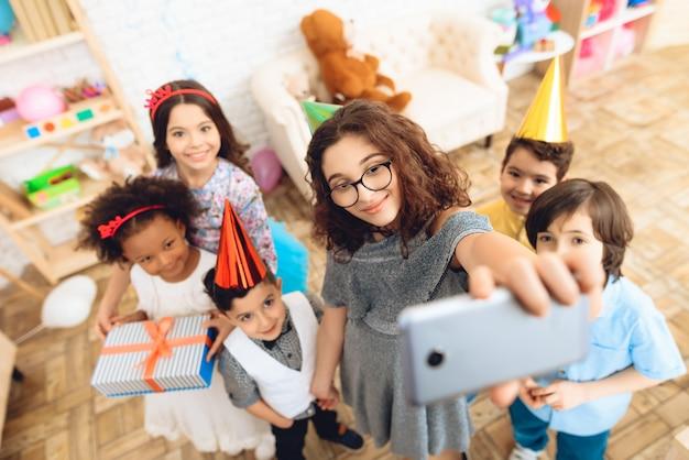 I bambini fanno selfie insieme alla festa di compleanno.