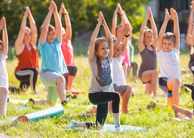 I bambini fanno yoga con un istruttore all'aperto.