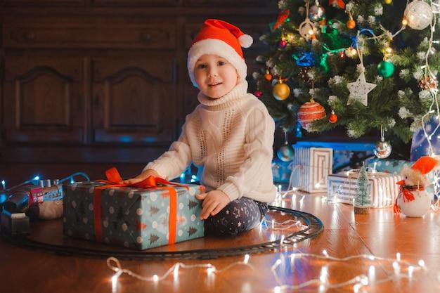 I bambini felici del ragazzino in cappello di santa con il regalo hanno natale o il nuovo anno.