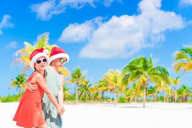 I bambini felici si divertono con il cappello di babbo natale durante le vacanze al mare di natale.