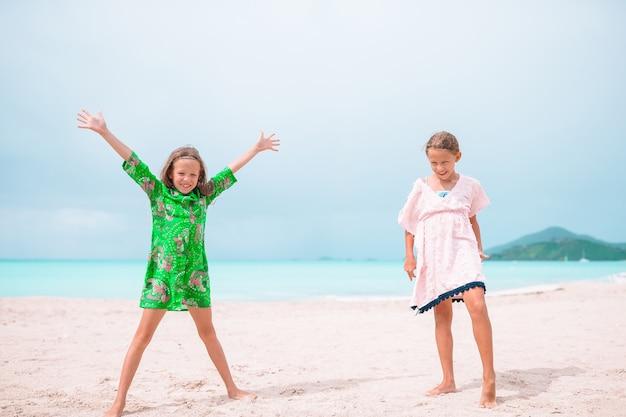 I bambini felici si divertono molto in spiaggia tropicale giocando insieme