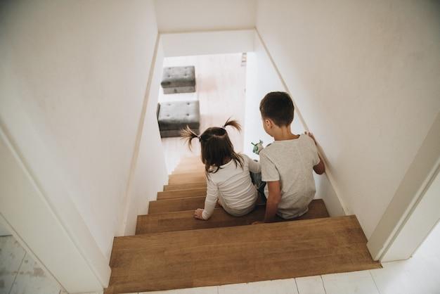 I bambini giocano a casa sulle scale. abbigliamento per la casa grigio. figlio e figlia fratello e sorella. siediti sui gradini.
