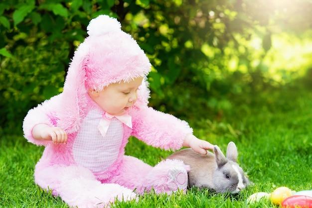 I bambini giocano con un vero coniglio. ridere bambino a caccia alle uova di pasqua con coniglietto da compagnia.