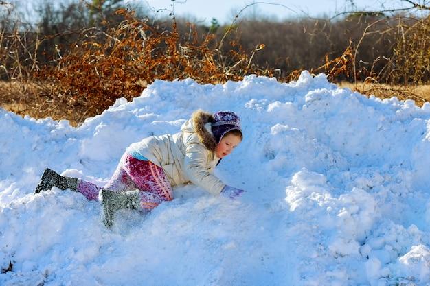 I bambini giocano fuori stagione invernale bambino felice che gioca nella neve vicino a una foresta