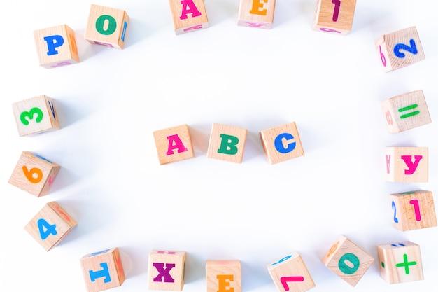 I bambini giocano i cuccioli di legno con lettere e numeri