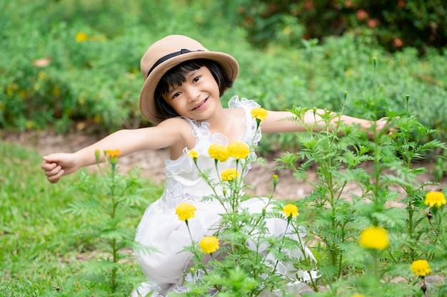 I bambini graziosi della ragazza si rinfrescano sul giardino floreale in parco