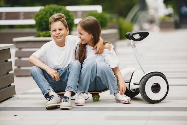 I bambini imparano a guidare hoverboard in un parco in una soleggiata giornata estiva